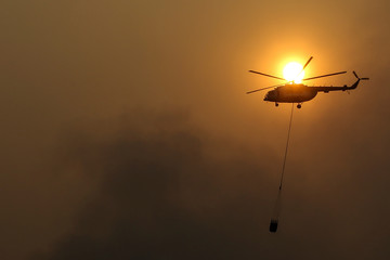 A helicopter from the National Disaster Management Agency (BNPB) waterbombs a ground fire in Indralaya Utara, near Palembang, South Sumatra