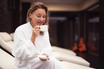 Sweet taste. Portrait of attractive lady with wet hair sitting on daybed at spa salon and holding cup of hot drink