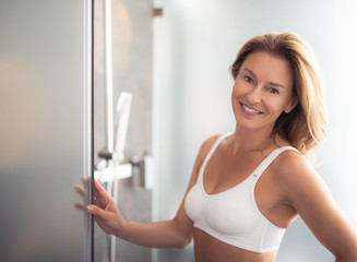 I am in good mood. Waist up portrait of charming lady holding door and smiling. She is wearing white sport bra