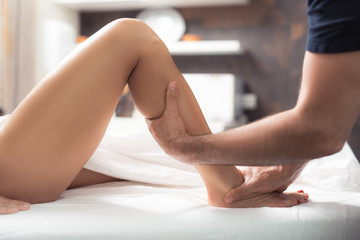 Beauty treatment. Close up of therapist hands massaging lady leg. She is lying on white sheets with bent knee