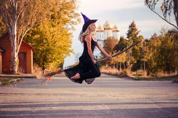Girl in Halloween costume flies on a broomstick