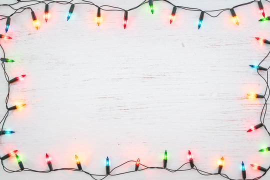 Christmas lights bulb frame decoration on white wood. Merry Christmas and New Year holiday background. top view