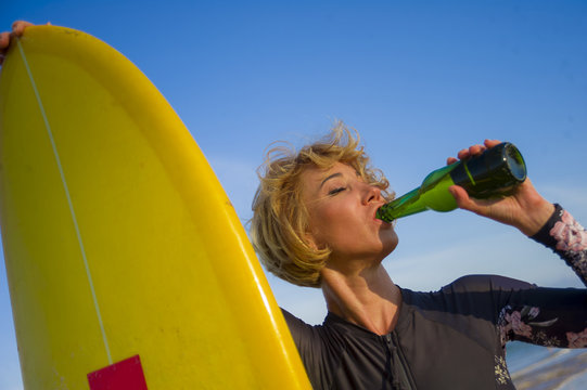 young sexy beautiful and happy surfer woman holding yellow surf board smiling cheerful drinking beer bottle enjoying summer holidays in tropical beach