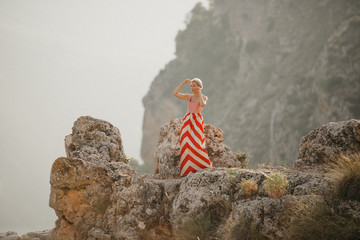 An attractive blonde lady in the red dress dancing on the top of the cliff with the mountain on the background. Mountain view. Evening in Spain