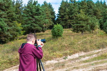 Young unidentifiable teenage boy taking landscape images with a camera on tripod near a pine forest.