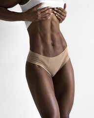 Female dark skin fitness athlete holding stomach showing abs and body