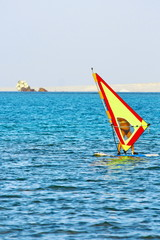 Windsurfer, blue sea and yellow sail. Surfer exercising in calm sea or ocean