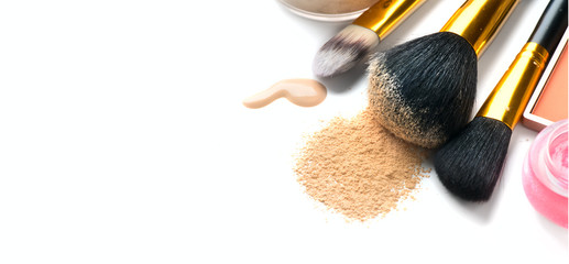 Cosmetic liquid foundation or cream, loose face powder, various brushes for apply makeup. Make up concealer smear and powder isolated on a white background. Products for professional face skin makeup Wall mural