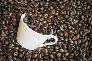 Coffee cup on the heap of fresh coffee beans