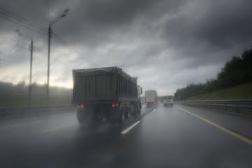 truck on wet asphalt after rain. Dark clouds on the sky