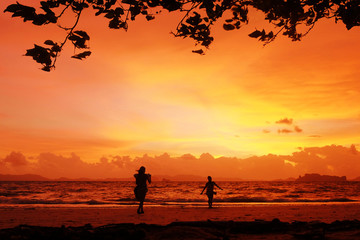 Photoshoot on sunset. Silhouettes of girls posing on the beach with crazy red sky on the background. Krabi, Thailand.