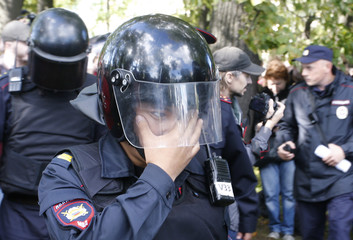 A policeman affected by tear gas covers his face during a rally against pension reforms in St. Petersburg