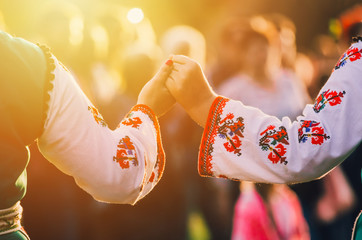 Girls in traditional Bulgarian ethnic costumes with red dresses and patterns on white shirts holding hands in the sunset. Concept of unity. Celebration Wall mural