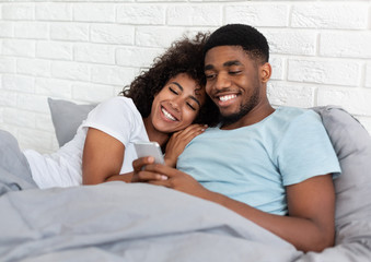 Smiling black millennial couple using smartphone on bed