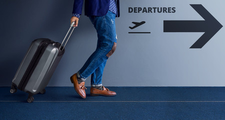 Traveling Concept, Young Traveler Walking with Suitcase and Follow the Departures Sign in the Airport