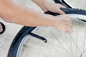 Hand of man change tire for bike by rubber plastics tool.