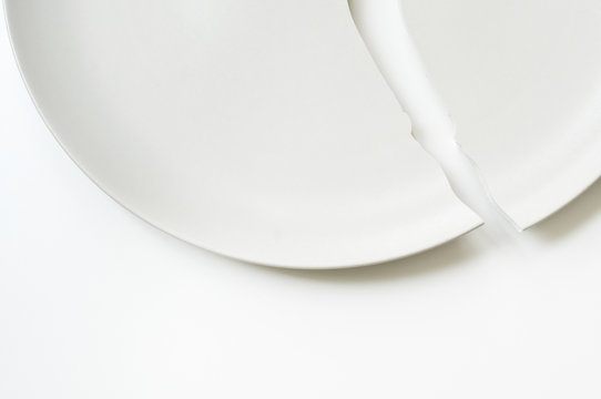 Cracked plate on white table.