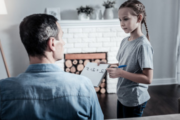 Homework. Cute pleasant schoolgirl showing notes to thr father while looking at him