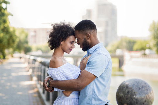 Loving african-american couple hugging on the bridge
