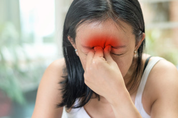 Sinus,Sinusitis, or rhinosinusitis concept. Asia woman suffer from headache, migraine, thick nasal mucus, and face pain symptoms.