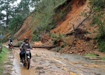 Motorists ride on motorcycles along a road, past a landslide after Typhoon Mangkhut hit Bokod, Benguet