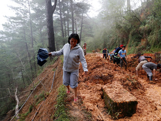 A resident walks on the side of a road as police officers and fire marshals clear debris and fallen trees caused by a landslide at the height of Typhoon Mangkhut that hit Bokod, Benguet