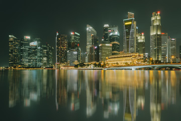 Singapore city skyline. Business district view. Downtown reflected in water at night in Marina Bay. Travel cityscape