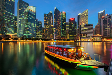 Singapore city skyline. Excursion cruise boat and business district view. downtown reflected in water at dusk in Marina Bay. Travel cityscape