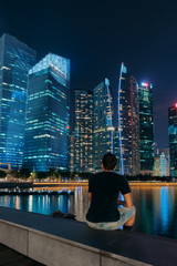 Singapore city skyline. Man is sitting near business district view. Downtown reflected in water at night in Marina Bay. Travel cityscape