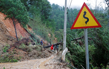 Government workers clear debris and fallen trees caused by a landslide at the height of Typhoon Mangkhut that hit Bokod, Benguet