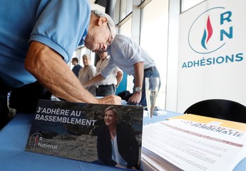 A man fills the membership form for French far-right National Rally (Rassemblement National) party, before party leader Marine Le Pen delivers her comeback speech in Frejus