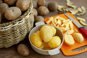 Boiled and raw potatoes. Boiled potatoes in a cup. A lot of potatoes in a wicker basket. Nerazannye vegetables on a cutting board. The process of cooking.