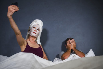 eccentric housewife with makeup facial mask and towel taking selfie in bed and husband with desperate face expression in weird man woman relationship concept