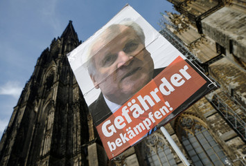 """A placard depicting Christian Social Union (CSU) leader Horst Seehofer and reading """"Fight the danger"""" is seen during a protest march against right-wing extremism in Cologne"""