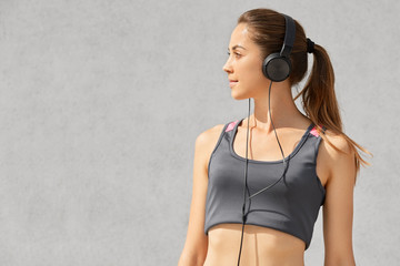 Sideways shot of dark haired female athlete with pony tail, listens radio or music in modern headphones, concentrated into distance, isolated over grey background with copy space for your text