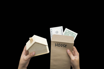 hand hold envelope with dollars money, save for house on black background