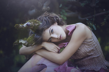 Portrait of girl enchanted Princess with horns. Girl Mystical creature fawn in shabby clothes in a fairy forest. Halloween concept ideas.