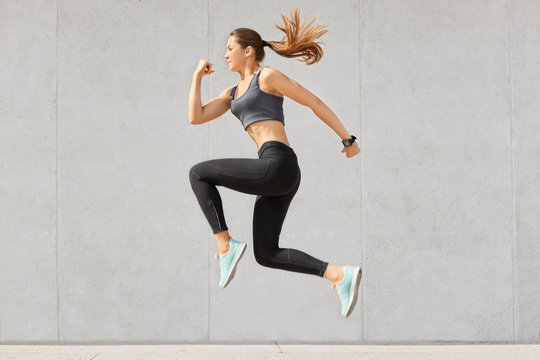 Active woman being full of energy, jumps high in air, wears sportsclothes, prepares for sport competitions, isolated over grey concrete wall. Female trainer busy with training. Gymnastics concept