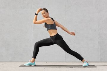 Athletic woman practices yoga, makes wide steps, shows good flexibility, poses against grey background, dressed in sportsclothes, isolated over grey concrete wall, checks pulse on smartwatch