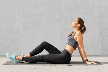 People, sport and relaxation concept. Relaxed fitness woman with perfect figure sits on exercise mat, keeps eyes closed, dreams about something after having morning workout or yoga practice.