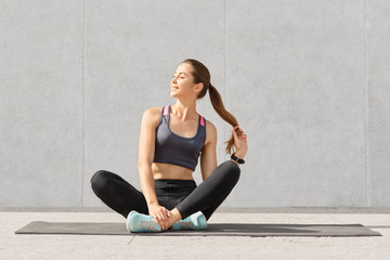 Relaxed beautiful Caucasian woman holds pony tail, sits crossed legs on fitness mat, being in high spirit poses against grey background. Active fitness couch rests after training in gym. Sport concept
