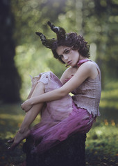 Girl enchanted Princess with horns. Girl Mystical fairy creature fawn in shabby clothes sitting on a stump in . Halloween concept ideas.