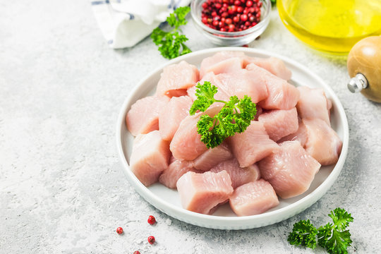 Raw meat cubes in a bowl with parsley, seasonings and olive oil. Selective focus, space for text.