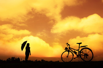 Silhouette woman is holding an umbrella, and cycling in the warm light