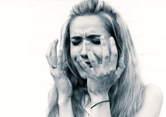 Young upset woman with raised arms on a light background. Negative emotions. Tinted photo.