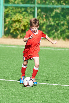 Boy soccer player with ball on football field