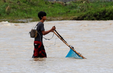 A man uses a net, operated by electricity from a car battery, to catch fish in a river a day after Typhoon Mangkhut hit Bambang
