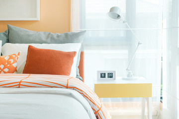White foldable reading lamp on night table next to bed in orange and gray bedding style