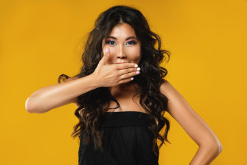 Asian woman with a beautiful curly hair and make-up on yellow background