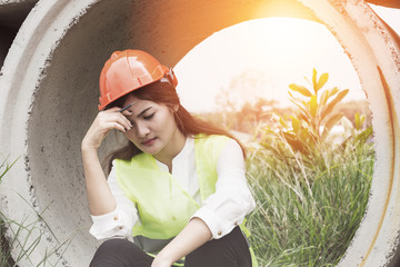 Stressed and tried of engineer Asian woman sitting on ground with white helmet after construction problem and lost job